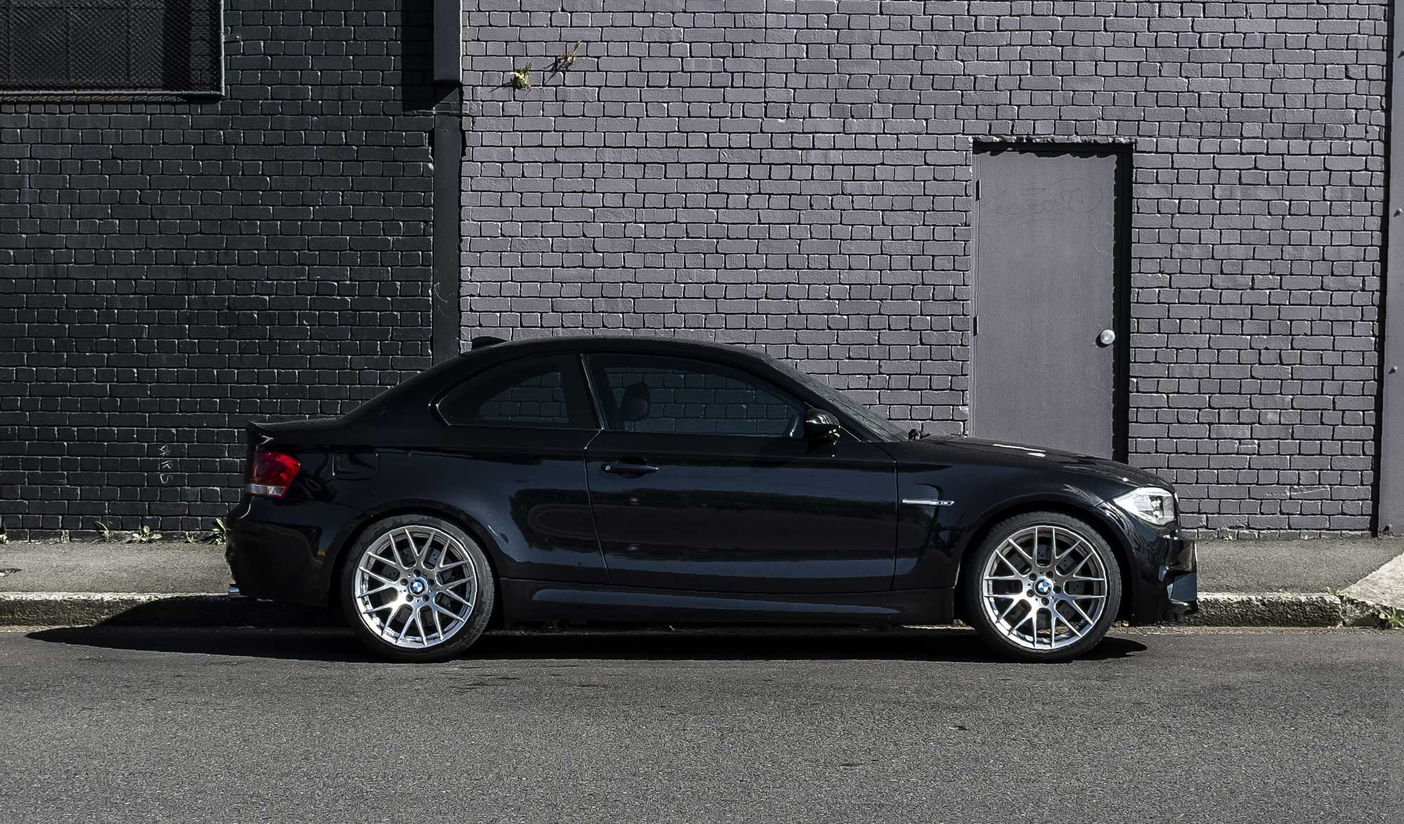 Black BMW 1M in front of a grey brick wall