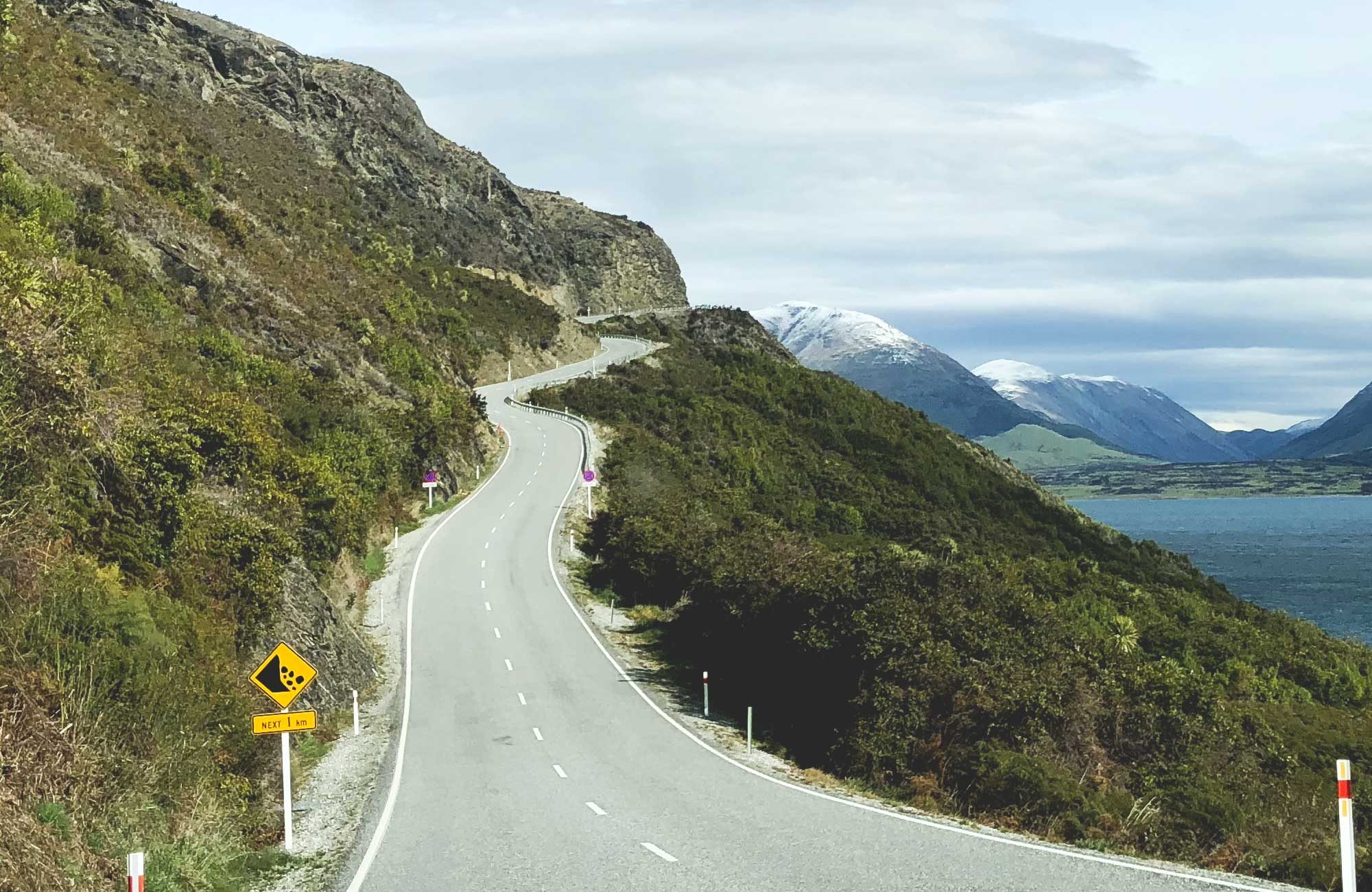 A twisty section of Queenstown to Glenorchy Road climbing up a mountain side with snow capped mountains in the background.