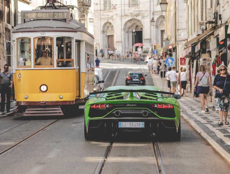 lamborghini aventador svj driving down a european street with a tram opposite