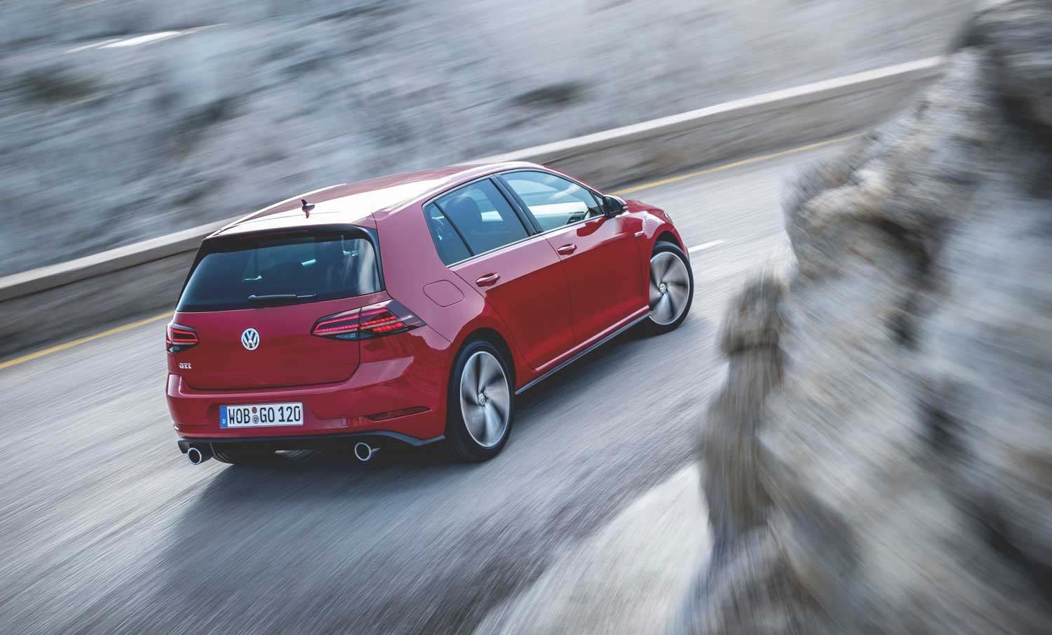 Red VW Golf GTI mk7 driving aggressively around a corner