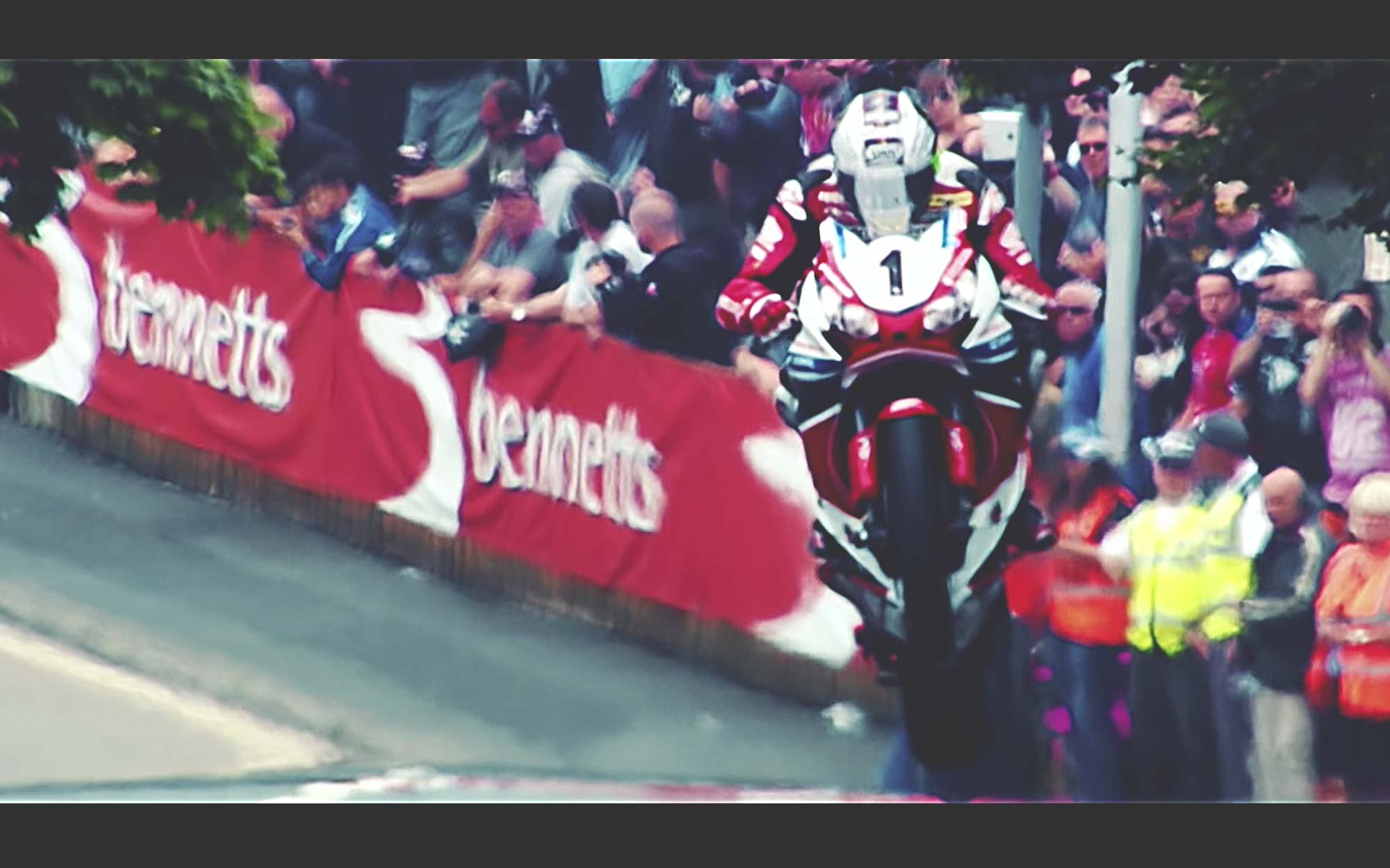 John McGuiness airborne over a crest in the Isle of Man TT as a crowd looks on in the background
