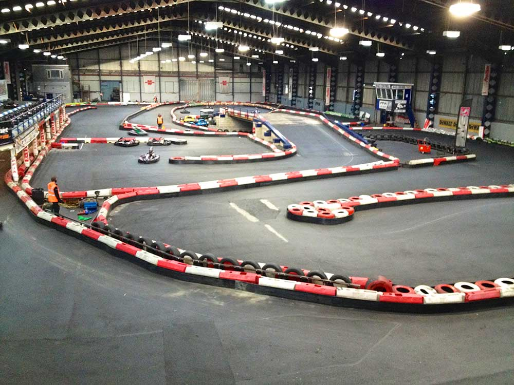 Indoor karting centre with karts racing around a circuit.